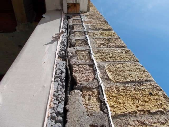 Asbestos felt bitumen in window wall void