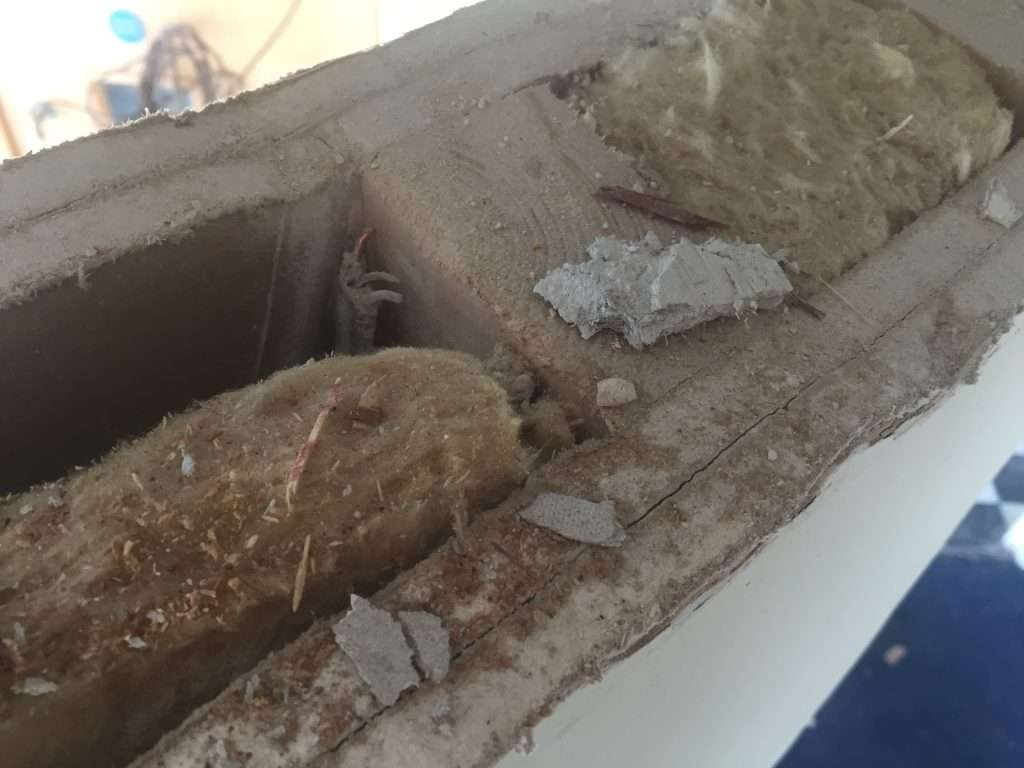 Asbestos insulating board debris on stud partition wall from damaged wall packers