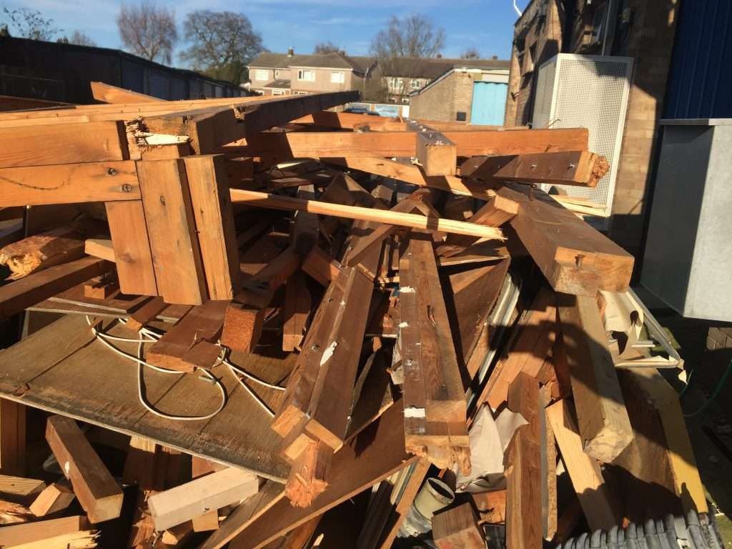 Asbestos insulating board debris to timber removed from building