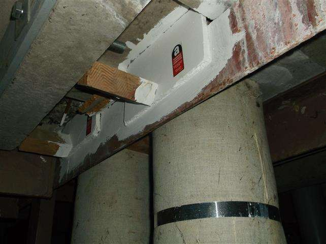Asbestos insulating board packer to beams in duct