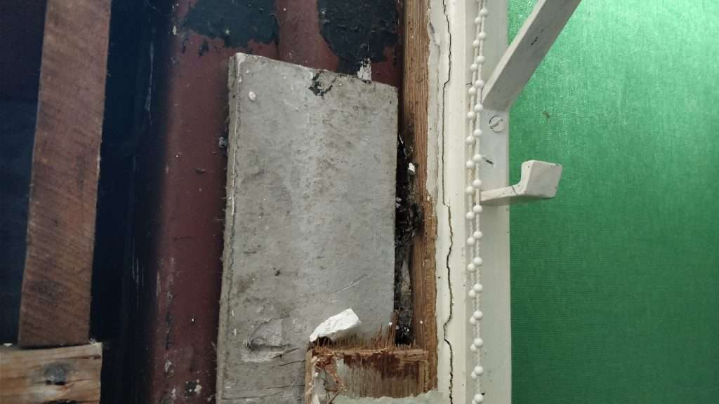 Asbestos insulating board packer to column within a school building