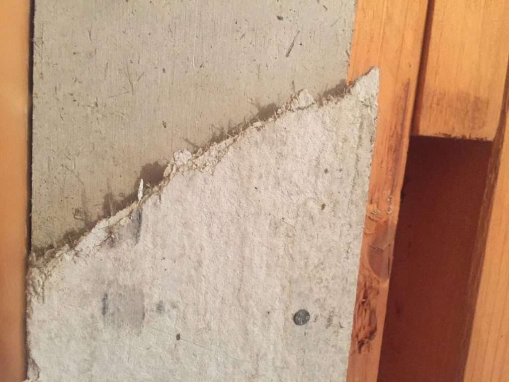 Asbestos insulating board panel to timber frame in warehouse