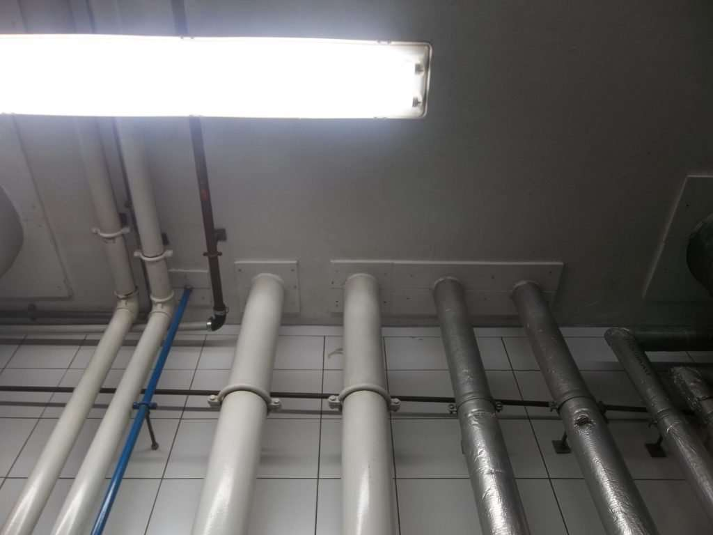 Asbestos insulating board panels around pipe penetrations in ceiling