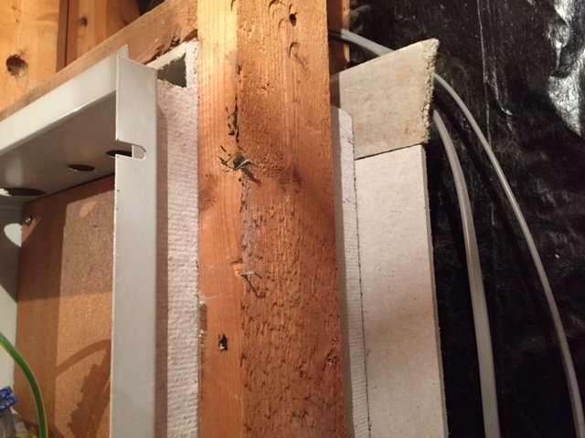 Asbestos millboard boxing around timber frame