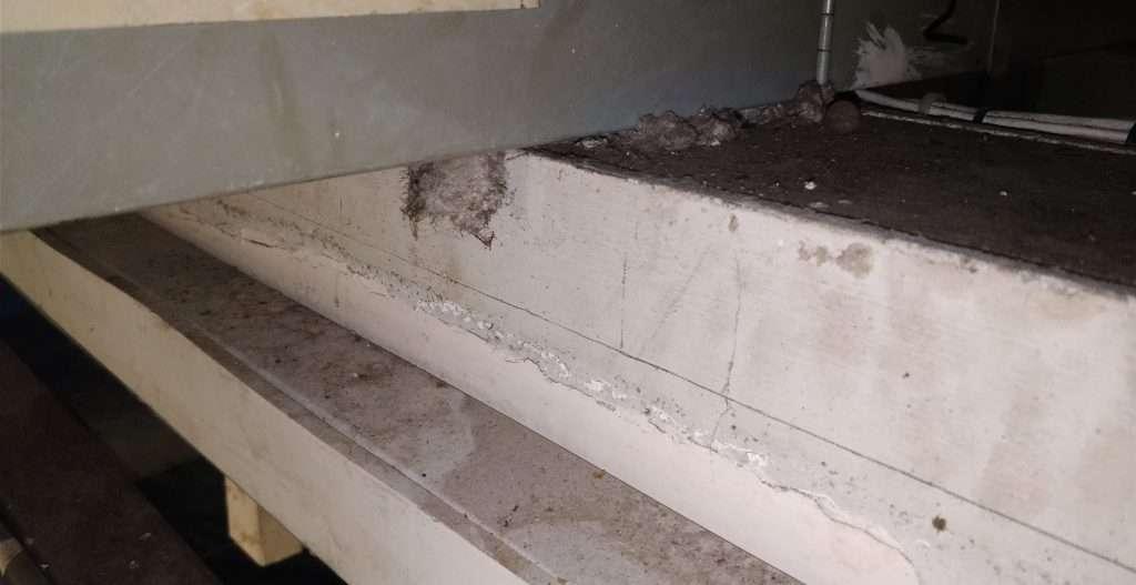 Asbestos spray coating debris sitting on top of ducting