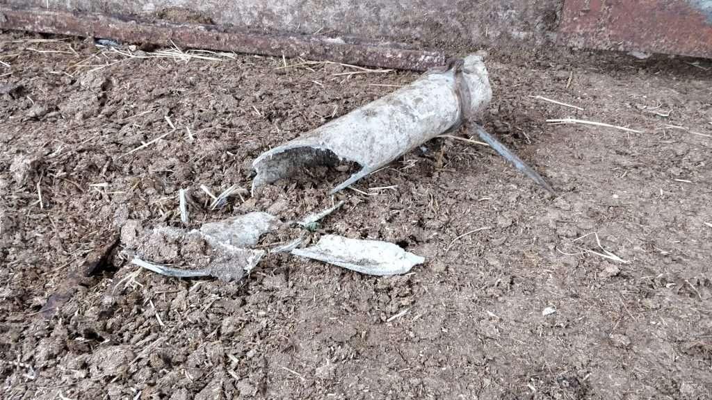 Broken asbestos cement pipe to floor at a farm
