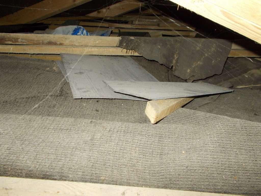 Broken asbestos cement roof tiles in loft of office