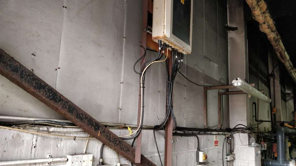 Unsealed asbestos insulating board within garage