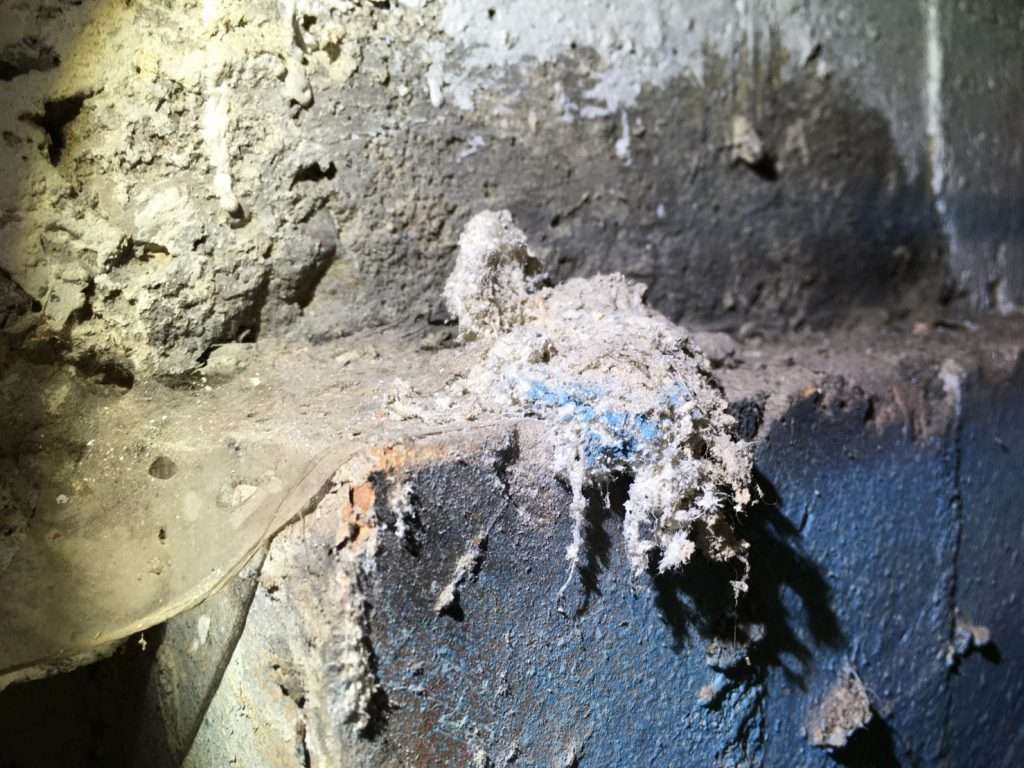 Unsealed asbestos insulation residue to wall
