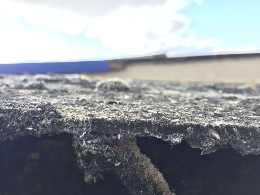 Weathered asbestos cement warehouse roof with chrysotile white asbestos fibres