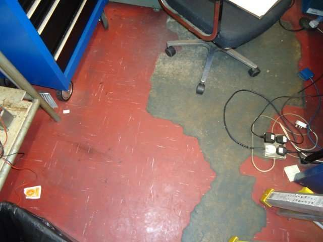 Worn through asbestos vinyl flooring in workshop