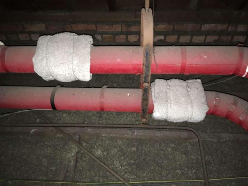 Woven asbestos blanket around pipe flanges